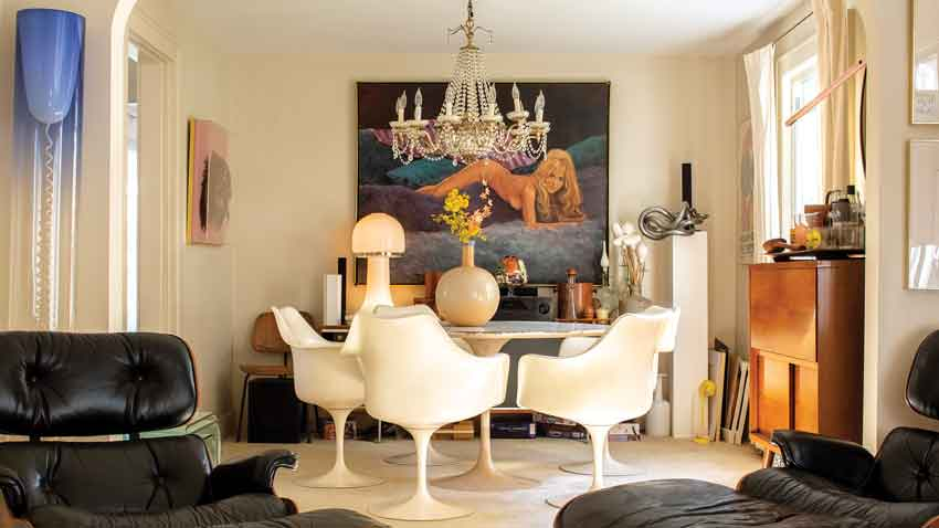 In the dining room, a 1970s-era nude by Alex Tavoularis peeks out over a Saarinen Tulip table and chairs, a cheekily suggestive 1960s glass mushroom lamp, and a bulbous 1970s vase from Portland Flea-For-All.