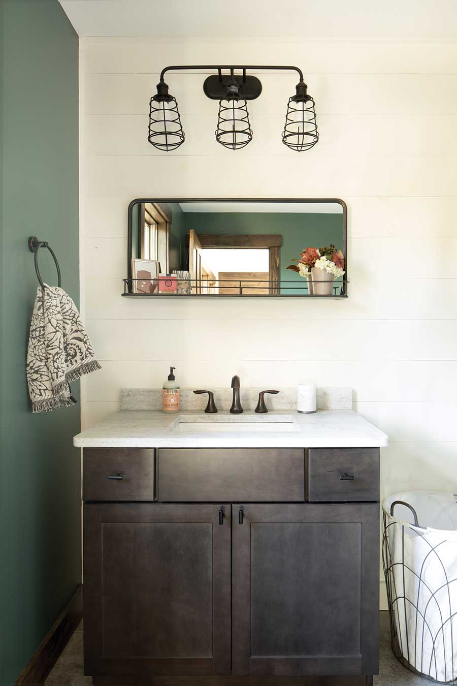 The primary bath combines a vanity, mirror, and sconce from Wayfair with the home's recurring green-and-white palette — and privacy.