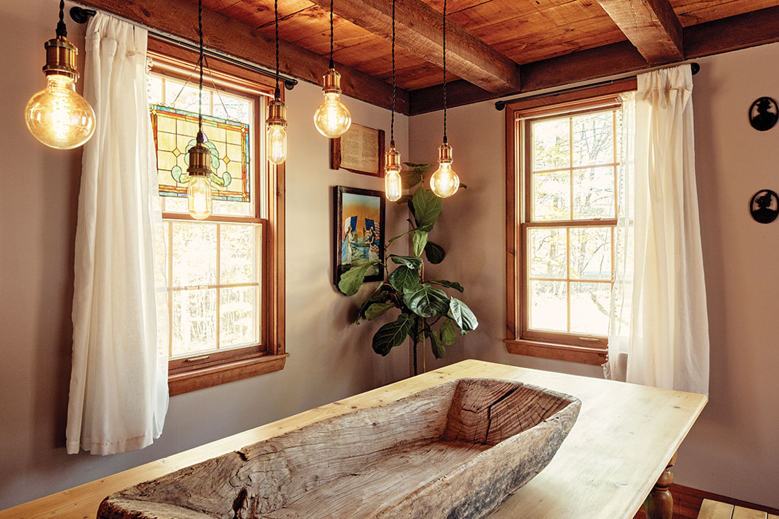 A light fixture composed of Edison bulbs suspended from a steel pipe crowns a pine table nestled between windows that frame the woodsy view.