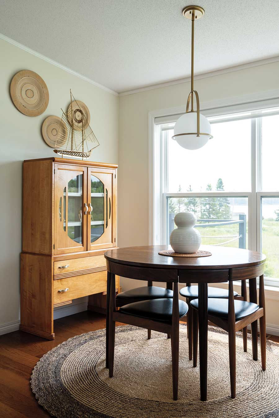 An Art Deco cabinet from Old Creamery Antique Mall in Ellsworth and a Hans Olsen Roundette table grace the pine-sided main cottage