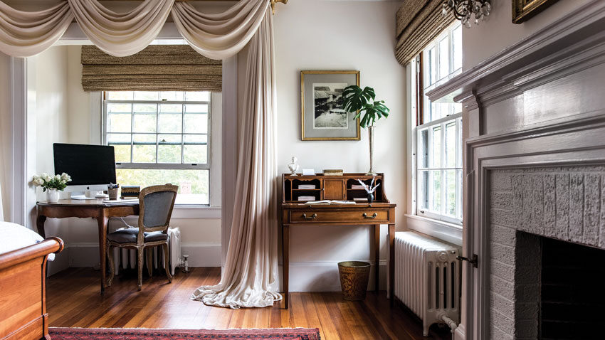 In the primary bedroom, blush-pink silk curtains blend with walls in Cream Froth by Benjamin Moore, and pick up tones in an antique rug.